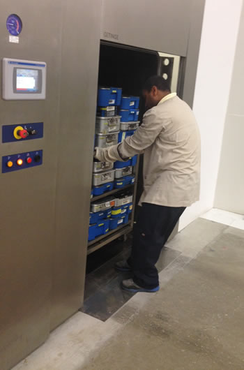 Stephen Foster, UPS Loaner Inbound Lead, moves medical devices out of autoclave, a decontamination process that uses steam heated at 300 degrees.
