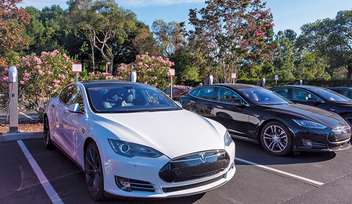 Tesla cars charging in their designated parking spaces at the Tesla headquarters in Palo Alto.
