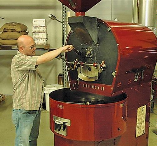 Fred Polzin, co-founder of Topeka-based PT's Coffee Roasting Co., works on a refurbished roaster that will increase capacity fourfold.