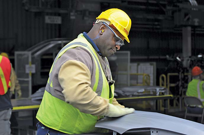 A Toyota team member inspects Corolla parts at the new plant in Blue Springs, Miss.