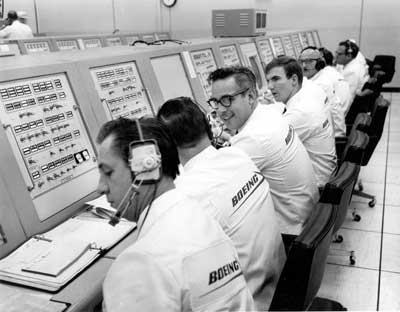 "Boeing's ties to Kennedy Space Center predate the complex receiving that name. Here a special Boeing crew dressed in ""ice cream"" suits monitors Saturn V launch preparations for Apollo."